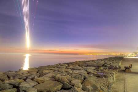 touch down: There is an aircraft just before the touch down and its light trail with long exposure Stock Photo