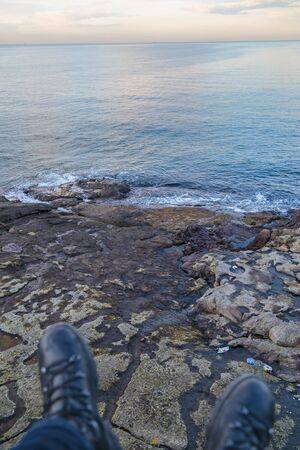 foots: Cliff of Istanbul, Northest Point of Bosphorus, man sitting on the rocks by the sea with his foots, focused groun defocused foots Stock Photo