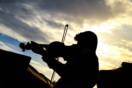 violinist: Silhouette of Violinist under the cloudy blue sky