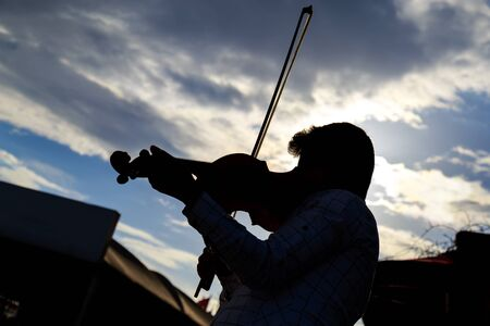 violinista: Silueta del violinista bajo el cielo azul nublado Foto de archivo