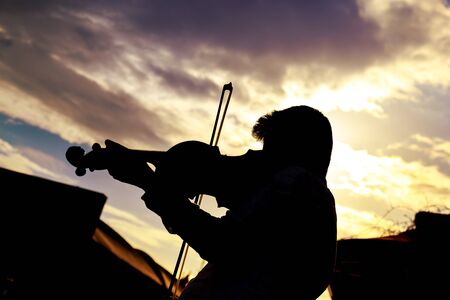 violinist: Silhouette of Violinist under the cloudy blue sky, puple filter applied