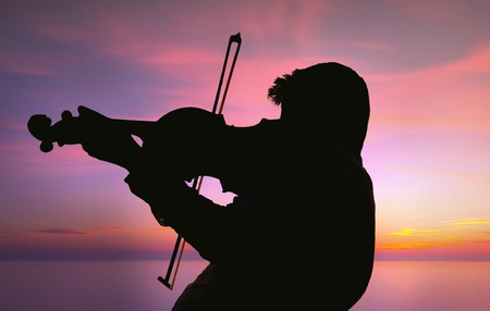 violin player: Silhouette of Violinist under the cloudy sky and near the long exposed sea via nd filter, purple filter applied