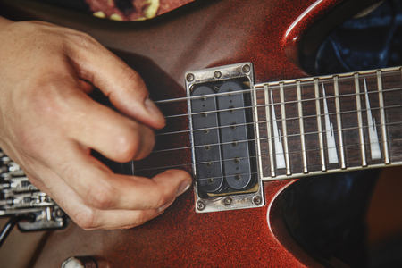 tremolo: man playing electric guitar close up view, very shallow depth of field image, cinematic effect applied Stock Photo