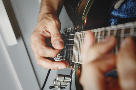 applied: man playing electric guitar close up view, very shallow depth of field image, cinematic effect applied Stock Photo