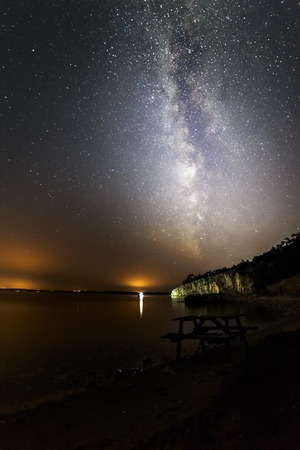 adds: Milky way near the sea, city lights adds sunset effect Stock Photo