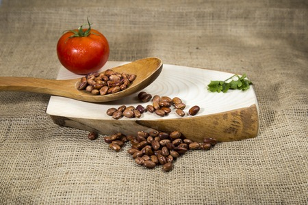 fava: Organic red dried beans over wooden tray and sackcloth, studio image Stock Photo