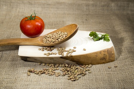 green lentil: Organic raw green lentil over wooden tray and sackcloth, studio image