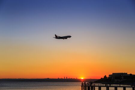 Silhouette of airplane approaching to runway, near to sea during sunset Stock Photo