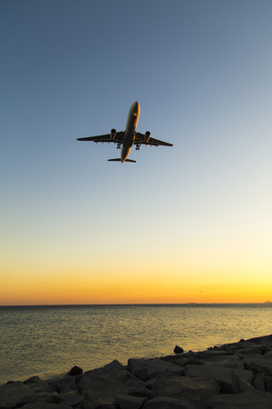 Silhouette of airplane approaching to runway
