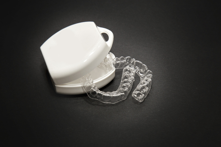 Isolated transparent teeth prosthesis with its box over black for design 写真素材