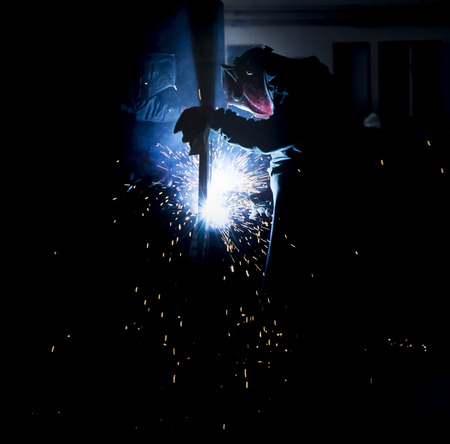 Anonymous labourer welding on iron Stock Photo