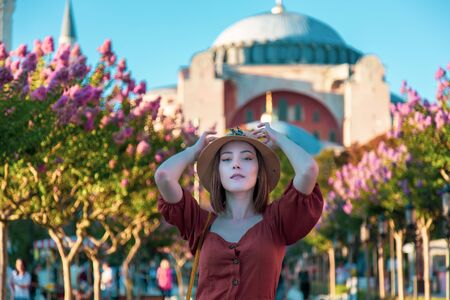 Beautiful girl with orange colored dress posing with Hagia Sophia during sunset from Istanbul Stock Photo