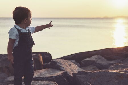 Toddler pointing up with his hand while posing in seaside during sunset with warm colors Foto de archivo