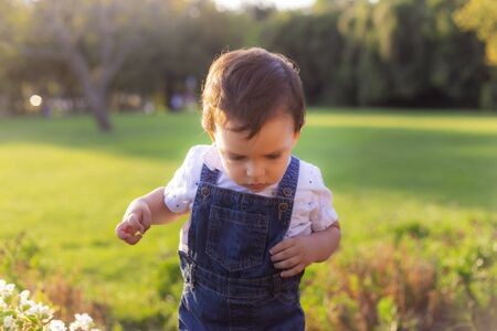 Toddler struggling to pass a hinder in green meadow