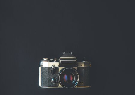 Flat lay top view of low key illuminated retro camera over black and deepless infinity background with copy space