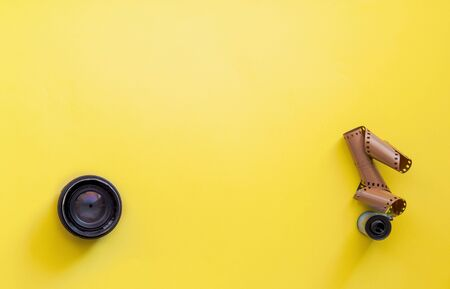 Flat lay view of retro camera lens and film strip over pastel coloured yellow background with copy space, pop art minimal style
