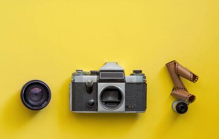 Flat lay view of retro camera, lens and film strip over pastel coloured yellow background with copy space, pop art minimal style