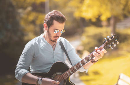 Anonymous man is playing a guitar at outside in autumn season with trendy orange colors, headless photo with copy space.