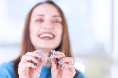 Beautiful smiling Turkish woman is holding an invisalign bracer, includes copy space