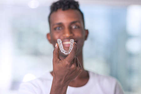 Handsome African Young Man Is Holding An Invisaligner, image with copyspace