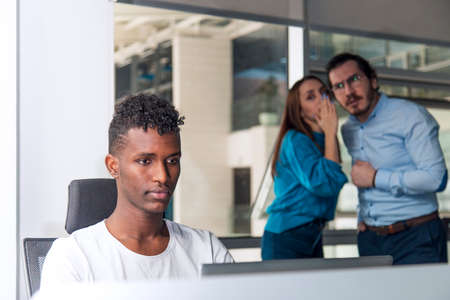 Black man is working on desk and there are two colleagues are gossiping at background behind of him Archivio Fotografico