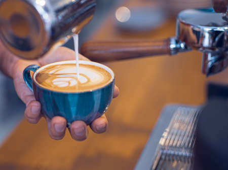 Artistic designed coffee latte view with coffee beans from a barista desk. Stock Photo