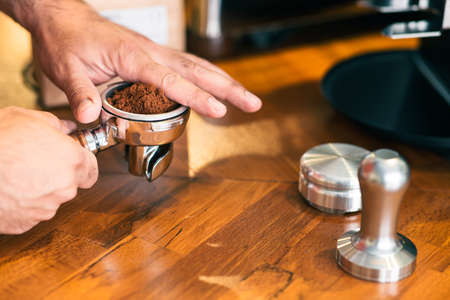 Barista holding portafilter with filled grinded coffee, closeup view includes copy space.