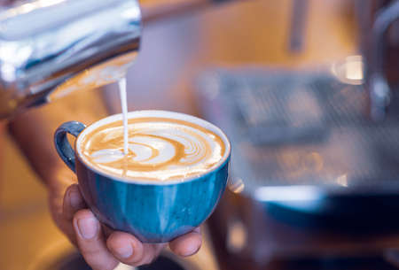 Barista preparing a latte in artistic mood, drawing a pattern to coffee. Stock Photo