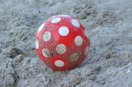 red ball with white points in the sand photo