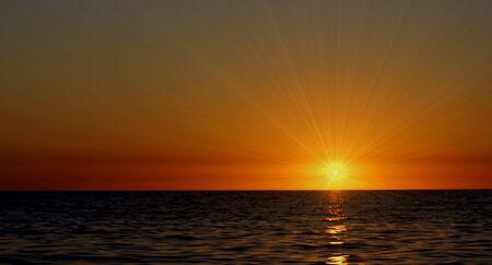 radiant sun dark sky and dark water