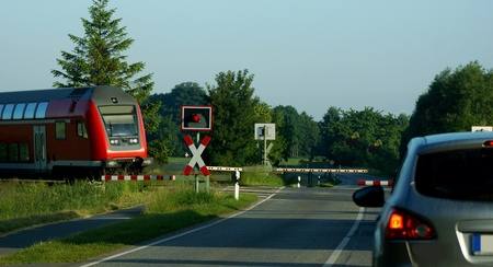 sicherheit: red railroad crossing a country road - down barrier