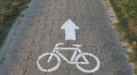 white road sign for cycle route on gray cobblestones on the dike