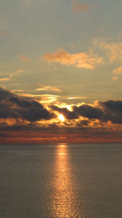 sun shining through the clouds at sunset on the water surface of the sea photo