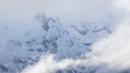 nice high mountains hiding in the sky with white clouds photo