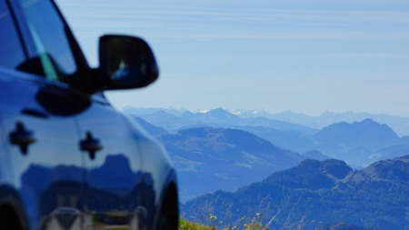 with the car in the mountains on the road and beautiful views to the peaks of the mountains photo