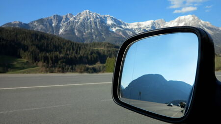 mountain pass: looking back on the road by the side mirror of the car