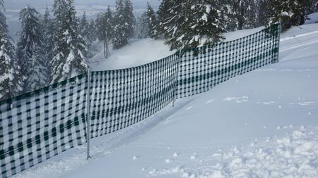 piste fence in the mountains and snow photo