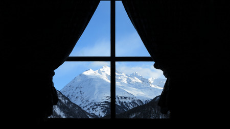 Mountain view with snow and peak and skiaus the window
