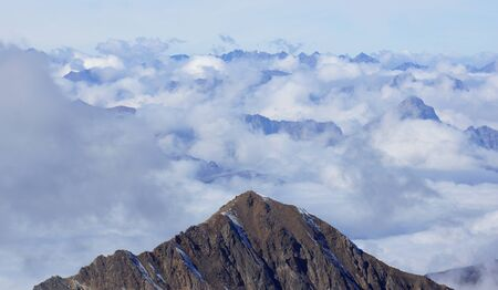 in low spirits: free view over the clouds and peaks of the mountains Stock Photo