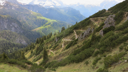 Small pedestrian serpentine road in the Alps and summits and summer