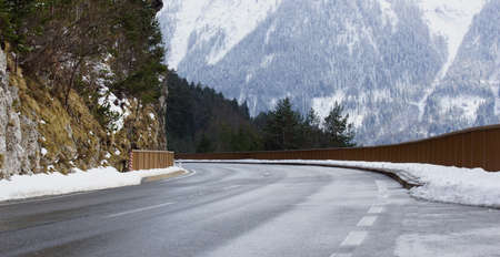 cleared road in the Alps and the snow and rocks
