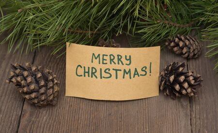 merry  christmas: Greeting card Merry Christmas written on kraft paper with fir tree with pine cones on a wooden background Stock Photo