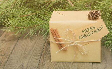 festive pine cones: Christmas present with greeting card Merry Christmas, fir tree, pine cones and cinnamon on wooden background in vintage style with copy space