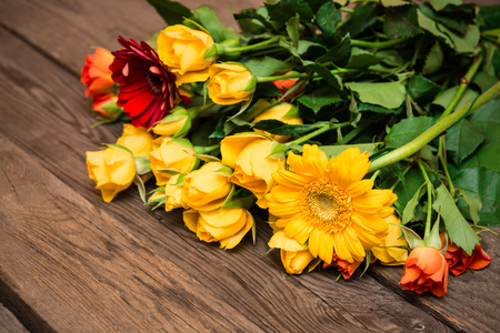 herbera: Yellow, orange roses and herberas on a wooden background. Women s day, Valentines Day, Mothers day. Copy space, selective focus