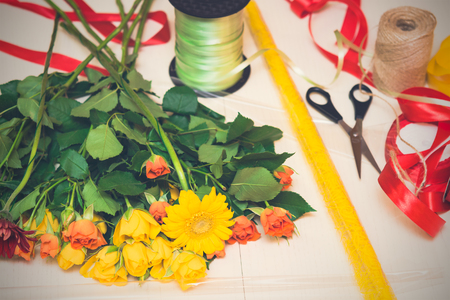 herbera: Workplace of florist, making bouquet. Yellow and orange roses on a wooden background. Women s day, Valentines Day, Mothers day. Copy space, selective focus, toned