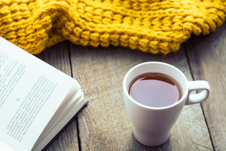 old desk: White cup of tea, book and scarf on old wooden desk. Selective focus, toned Stock Photo
