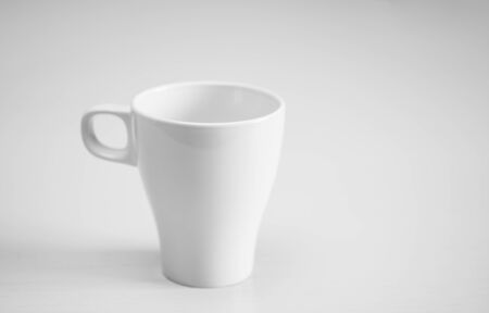 horizontal format: White cup on light wooden table.  Selective focus. Horizontal format.