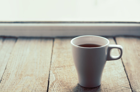 horizontal format: White cup on old wooden table. Horizontal format. Selective focus, toned