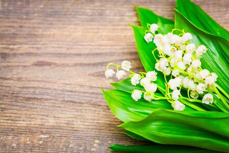 Bouquet of lilies of the valley on the wooden background. Spring background. Summer background. Selective focus