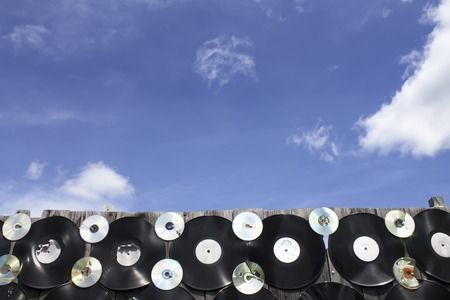 crack: Vinyl and cd screwed to a fence against a blue sky background